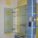 Встроенные стеклянные полочки с дверкой для ванной комнаты.